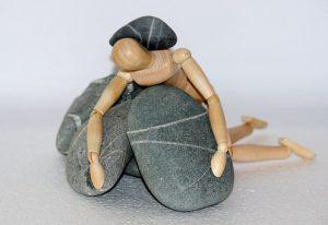figur-klemt-under-sten